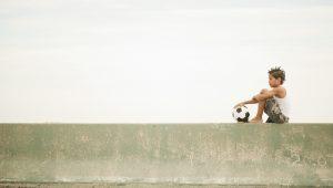 Nova geração pensando no futuro, garoto com uma bola sonhando sobre seu futuro profissional