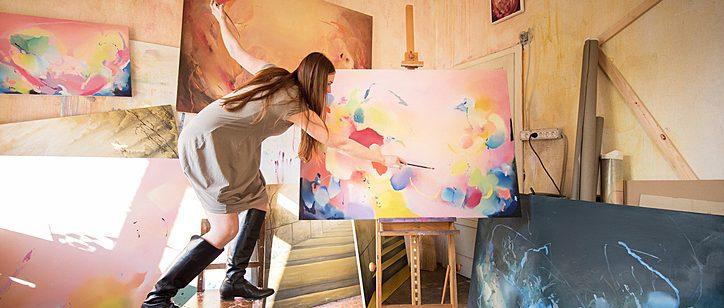 mulher correndo risco fazendo o que ama. Pintando uma grande tela em cima de uma cadeira.
