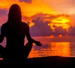 mulher meditando em frente ao mar no pôr do sol