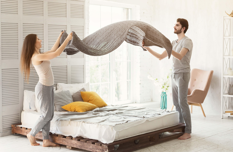 casal-homem-mulher-arrumando-a-cama