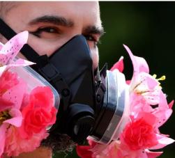 homem usando máscara de proteção com flores ao redor