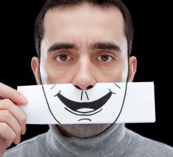Homem sem expressão segurando um sorriso desenhado em papel no rosto.